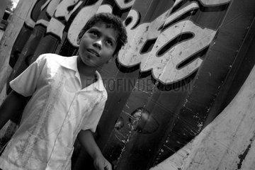 Junge vor einer Coca-Cola Werbetafel