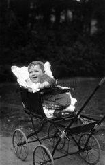 Lachendes Kind in Kinderwagen  1910