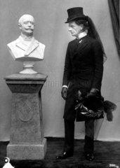 Herr mit Trauerzylinder neben Bueste Otto von Bismarcks