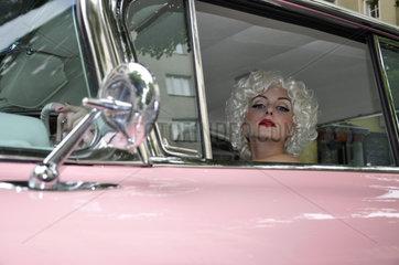 Frau am Steuer eines fuenziger Jahre Autos
