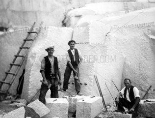 Drei Maenner arbeiten im Steinbruch
