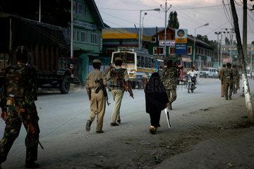 Eine alte Frau auf der Hauptstrasse  umgeben von Mitgliedern von verschiedenen indischen Armeeeinheiten und Polizei aus Kaschmir.