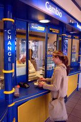 Eine Frau beim Geldwechseln in einer Wechselstube am Bahnhof Zoo.