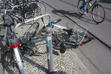 umgekippte Fahrraeder neben Strassenbahnschiene und vorbeifahrendem Radfahrer