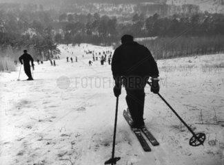 Mann faehrt Piste hinunter und blickt in ein Tal voller Skifahrer