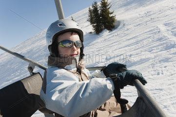 Boy riding ski lift at ski resort