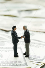 Male figurines shaking hands on pile of one hundred dollar bills