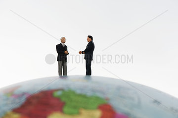Businessman figurines standing on top of globe