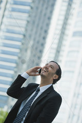 Business executive using cell phone outdoors