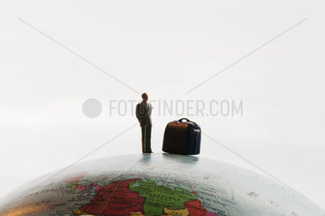 Businessman figurine with luggage standing on top of globe
