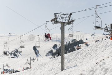 Skiers riding on ski lift at ski resort