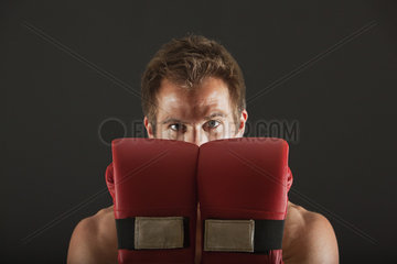 Boxer holding up gloves in front of face in defensive position