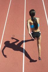 Female athlete running on track  focus on shadow