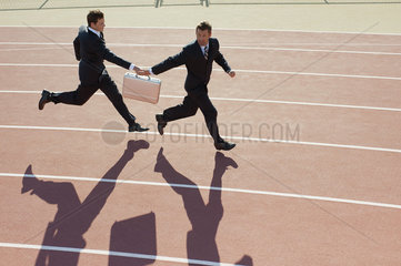 Businessmen passing briefcase while running on running track