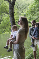 Family in woods looking at river  focus on mother holding baby girl