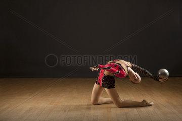 Gymnast bending backwards holding ball