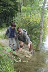 Father and son by river