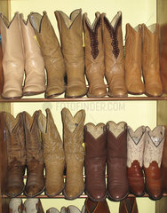 Rack of cowboy boots in thrift store
