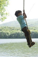 Boy hanging from rope over river