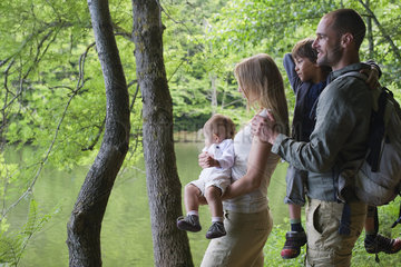 Family in woods looking at river
