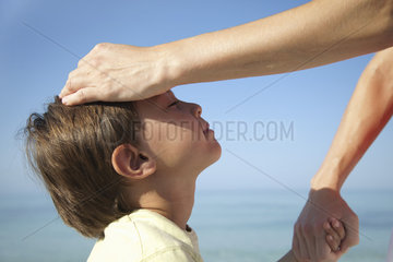 Mother's hand on boy's head