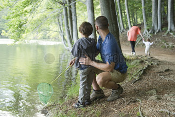 Father and son fishing in woods  both looking away