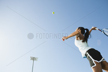 Female tennis player serving ball  low angle view
