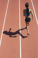 Female athlete running on track  rear view