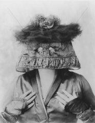 Frau mit Lampenschirm und Vogelnest auf dem Kopf