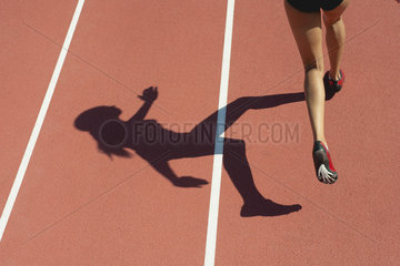 Female athlete running on track  low section  focus on shadow