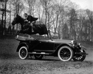 Reiter springt ueber ein Oldtimer