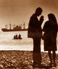 Italien - Genua Paar am Strand mit Schiff im Hintergrund