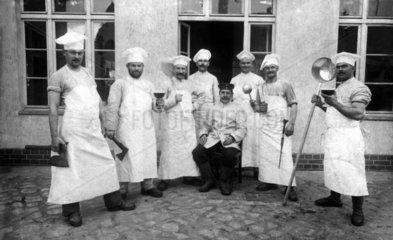 Koeche posieren mit Kuechengeraeten vor Kochschule 1914