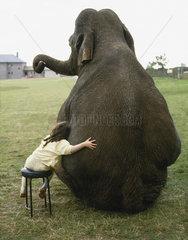 Elefant sitzt neben Maedchen