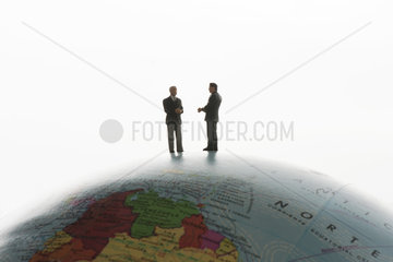 Businessman figurines standing on top of globe  silhouette