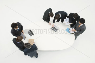Business associates working together in groups around table