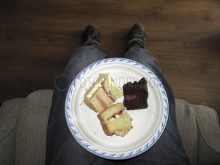 Plate of cake slices on man's lap  directly above
