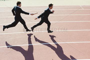 Businessmen running relay race