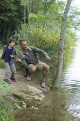Father and son throwing pebbles into river