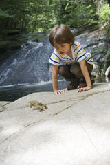Boy crouching on rock looking at frog jump