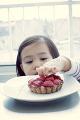 Little girl sticking fingers in fruit tart