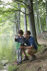Father and son fishing  boy staring at tiny fish in hand