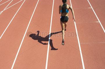 Female athlete running on track