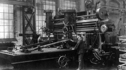 Arbeiter arbeiten an einer Maschine 1910-20