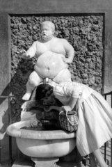 Frau trinkt aus Brunnen