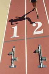 Starting blocks on tracks  athlete leaving starting line