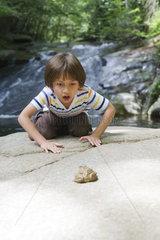 Boy kneeling on rock looking at frog