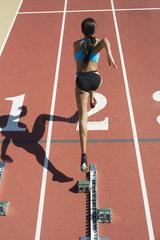 Female athlete leaving starting line  rear view