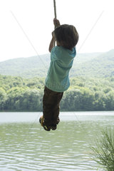 Boy hanging from rope over river  rear view