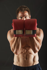 Barechested boxer holding up gloves in front of face in defensive position